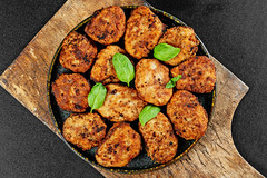 Juicy delicious meat cutlets on a old wooden kitchen board, top view