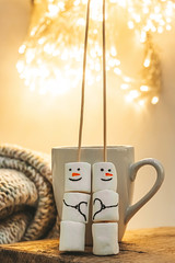 Marshmallow snowmen with a cup and beautiful bokeh of glowing garlands