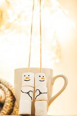 Christmas background with delicious marshmallow snowmen on bokeh background