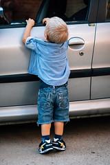 Curious young boy reaching through the car window