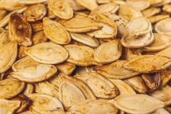 Roasted pumpkin seeds background, close-up