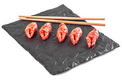 Crab claws marinated in a spicy sauce with herbs on a black stone tray