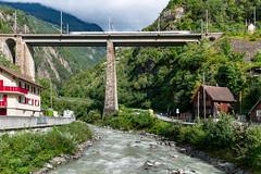 Swiss train speeding on an old tall brick bridge