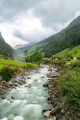 Mountain river flow in Swiss mountains disappearing in clouds