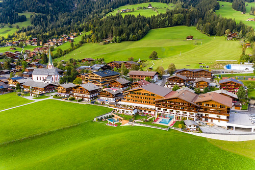 Wooden holiday homes and a church surrounded by green landscape in Alpbach in Tyrol