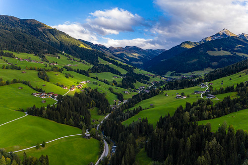 Alpbach: An alpine village with green hills, wooden houses and huge mountain peaks in Tyrol in Austria