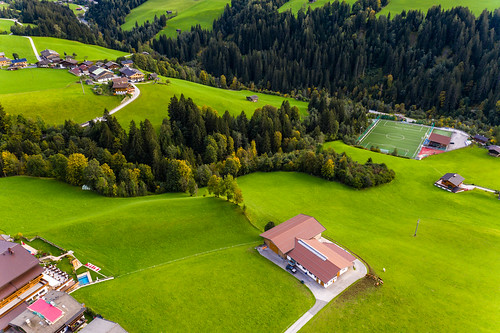 Green landscape with a few houses, a football court and the forest in Alpbach in autumn