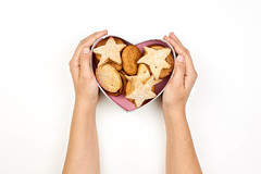 Female hands holding heart-shaped box with sweet cookies