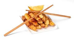 Fried fish sticks with a slice of lemon and chopsticks