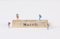 Miniature travelers and wooden block with June and March text on white background
