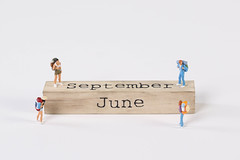 Miniature travelers and wooden block with September and June text on white background
