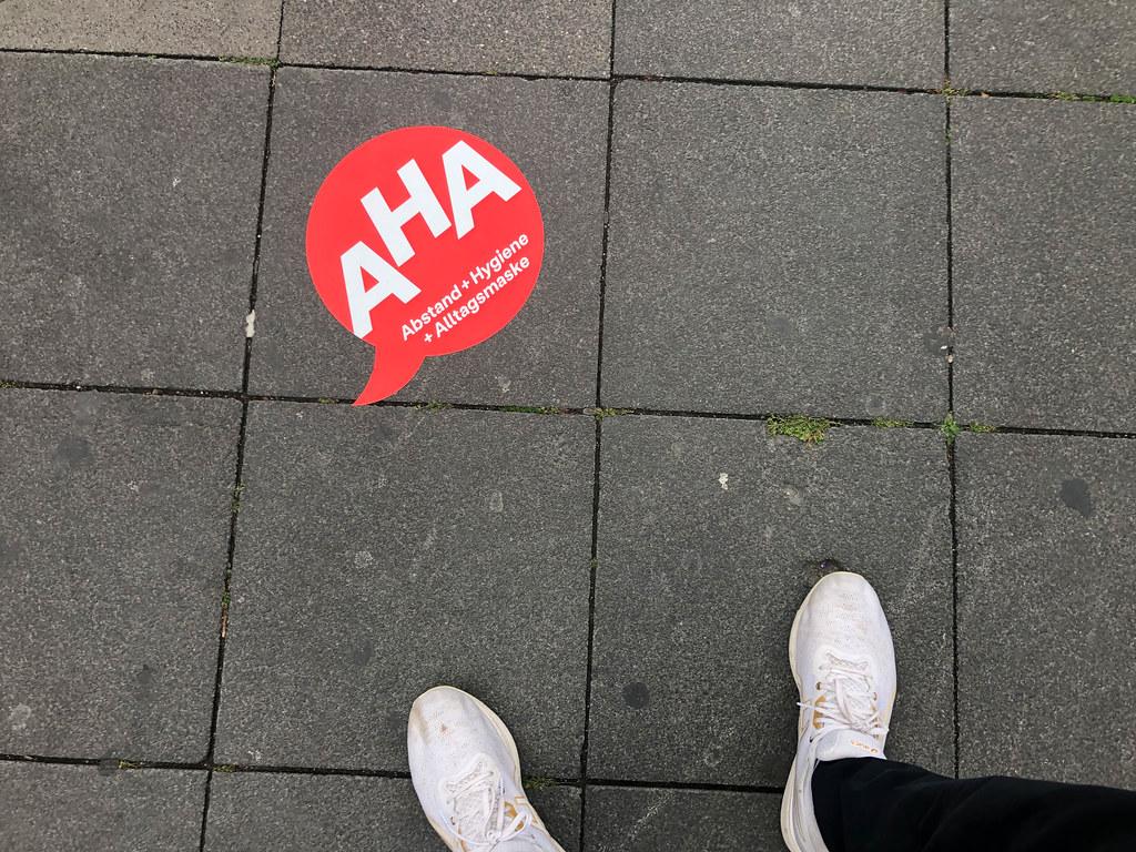 Füße und Sticker auf der Straße mit der AHA-Formel für den Corona-Alltag (Abstand, Hygiene, Alltagsmaske)