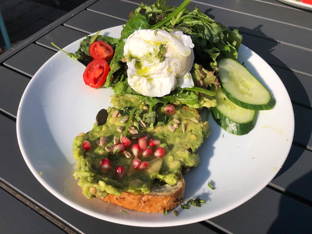 Toast mit Avocado, Granatapfelkernen und Kräutern, mit Gurken, Salat und Cherry-tomaten serviert