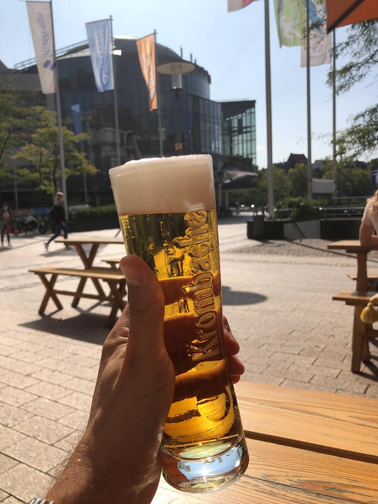Prost! Ein Krombacher vom Fass in der Hand an einem sonnigen Tag beim Media Park in Köln