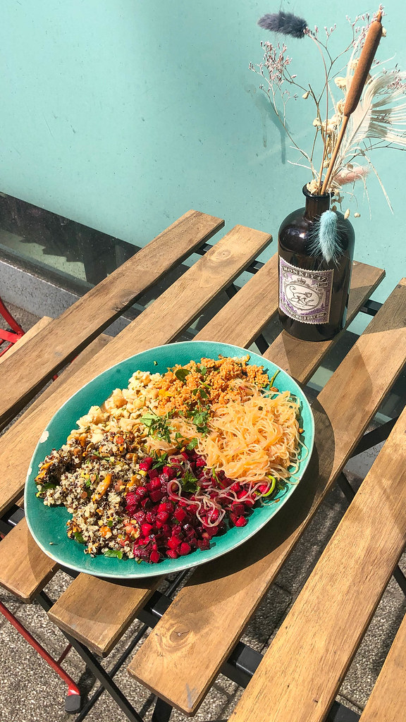 Rich vegan bowl with couscous, cauliflower salad, beetroot, pasta and quinoa served on blue plate
