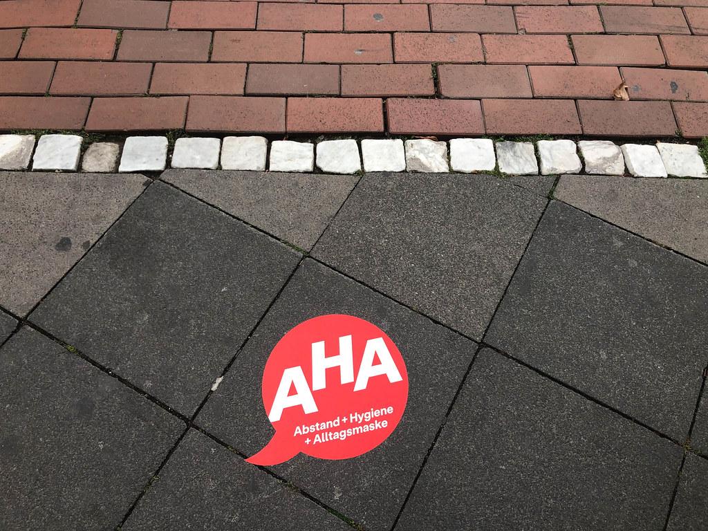 Ein roter Aufkleber mit dem Corona-Mantra AHA (Abstand + Hygiene + Alltagsmaske) auf dem Boden