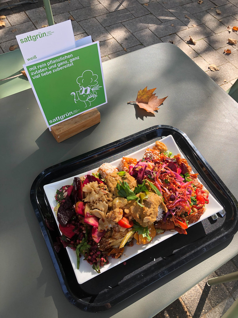 Eating at an outdoor table from a rich plate at the Sattgrün vegan buffet in Cologne
