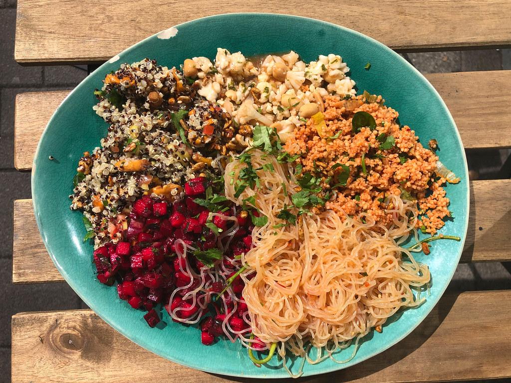Obene Aufnahme von reichhaltigem veganen Bowl mit Couscous, Blumenkohlsalat, Rote Beete und Nudeln