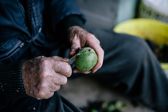 Man peeling walnut skin with a knife.
