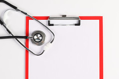 High angle view of clipboard with white paper and stethoscope on white surface