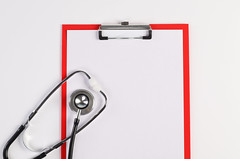 High angle view of clipboard with white paper and stethoscope on white background