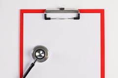 Clipboard with white paper and stethoscope on White surface