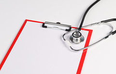 Blank medical clipboard with stethoscope on white background.
