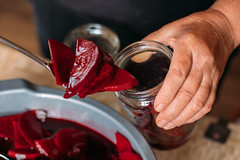 Person putting beetroot in a transparent glass jar for winter storage. Preparing pickled beetroot