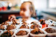 Girl sitting in front of a tray full of freshly baked chocolate cupcakes