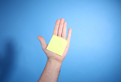 Yellow blank sticky note on palm of hand isolated on blue background with copy space