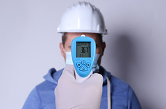 Hand with surgical latex gloves holding infrared thermometer gun and aiming it at a man's forehead with hard hat. Screen shows 36.7 degree celsius
