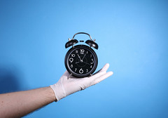 Alarm clock on the palm of a hand with surgical gloves on blue background