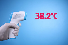 Hand with gloves holding non-contact infrared thermometer on blue background with red text 38.2 degree celsius
