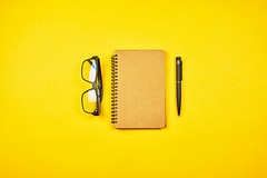 A writer's workspace. Notepad with eyeglasses on yellow background