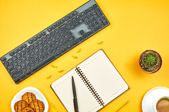 An open notebook, coffee mug and cookies on work desk