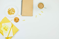 Notepads, a cup of coffee and oatmeal cookie on white