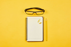 Starting a diary. Open notepad with eyeglasses on yellow background