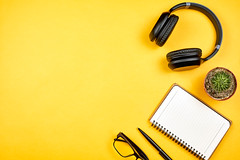 Notebook with wireless headphones on a yellow desk