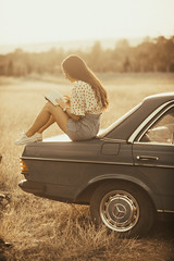 Woman sitting on a trunk of an old vintage car and reading a book.
