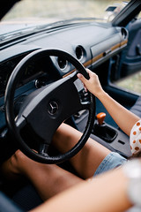 Woman sitting on the front seat of a car and holding a steering wheel.