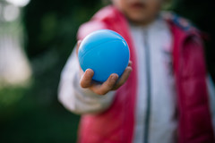 Little girl holds blue plastic ball in a summer park.