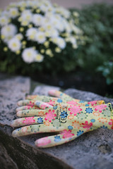 Garden gloves on concrete with flowers background.