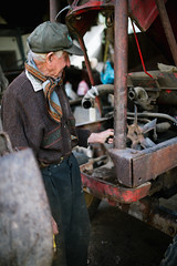 Old man servicing an old tractor.