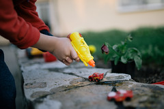 Young kid washing his red car miniatures with a water gun.
