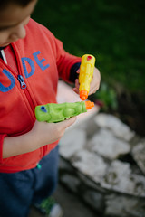 Young boy playing with two water guns.
