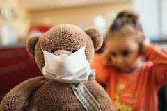 Teddy bear wearing a face mask in front of a girl with hands on her head.