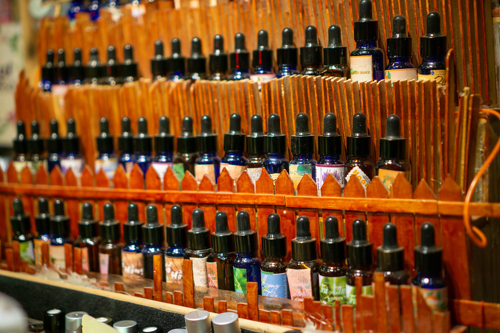 Different Essence Oils displayed on a Wooden Shelf in a Shop