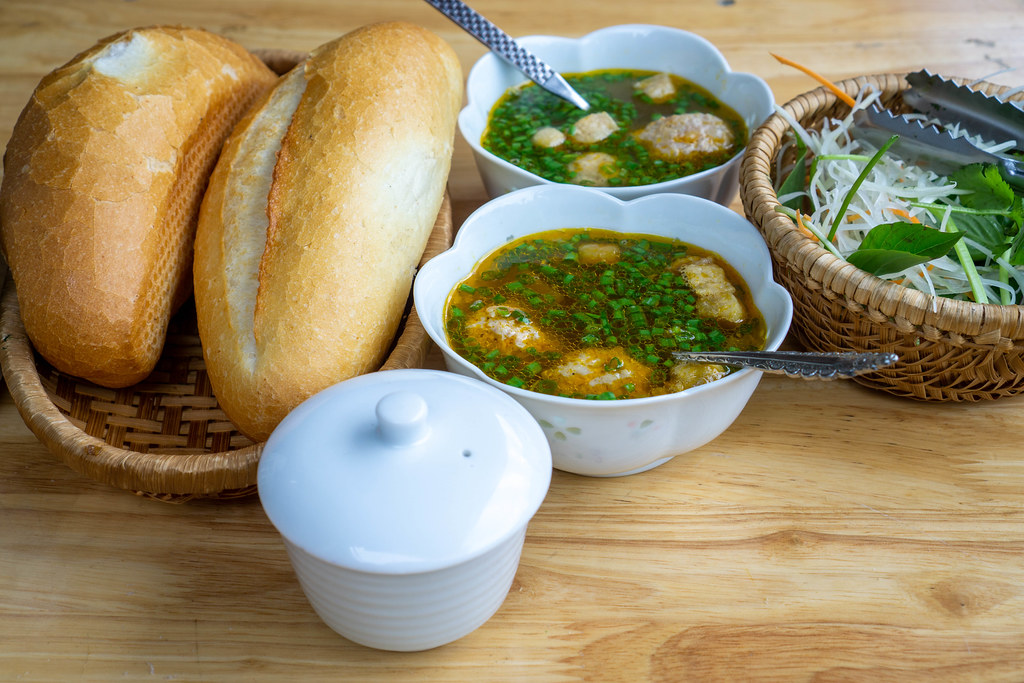 Vietnamese Breakfast Banh Mi with Meatballs and Herbs on a Wooden Table