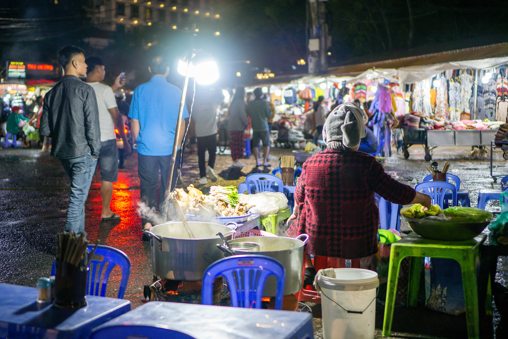 Street Food Noodle Soup in front of Clothing Stores at the Night Market in Dalat, Vietnam