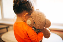 Young girl hugging a stuffed teddy bear.